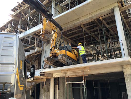 Ανέβασμα μίνι τσαπάκι με γερανό στον 1ο όροφο οικοδομής για εργασίες στο πίσω μέρος του πίσω μέρος του κτηρίου.